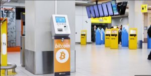 """Port lotniczy Schiphol w Amsterdamie jako pierwszy w Europie zainstalował """"bankomat Bitcoin""""  Wymianę """"lokalnych"""" euro na """"globalne"""" kryptowaluty."""